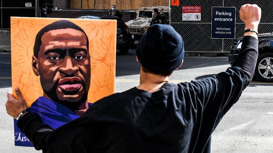 Manifestante segura um retrato de George Floyd em frente ao tribunal onde o caso é julgado em Minneapolis (EUA) - Chandan Khanna/AFP