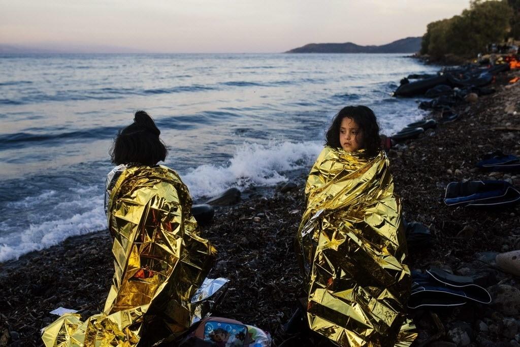 15.out.2015 - Crianças esperam na praia enroladas em capas térmicas após desembarcarem com outros refugiados em na ilha de Lesbos, na Grécia. De acordo com a agência de segurança das fronteiras da UE (União Europeia), a Frontex, um total de 710 mil pessoas entraram na região pela Grécia e Itália desde janeiro deste ano, a maioria afegãos e sírios