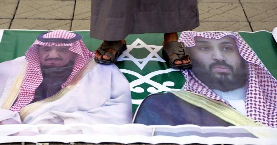 7.jan.2016 - Homem do movimento xiita houthi pisa em bandeira estilizada com a imagem do rei saudita, Salman bin Abdelaziz, e de seu filho durante um protesto contra a Arábia Saudita na embaixada da Arábia Saudita em Sanaa, no Iêmen. A execução do clérigo xiita Nimr al Nimr Baqir em 2 de janeiro pelas autoridades da Arábia Saudita, um país de maioria sunita, tem causado muitos protestos em países como Irã e Iêmen