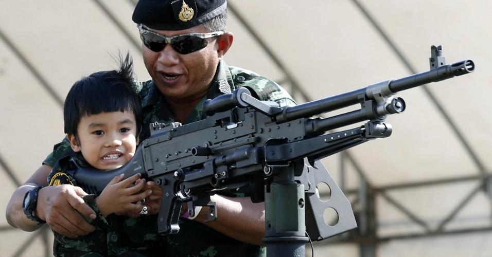 9.jan.2016 - Garoto tailandês empunha metralhadora acompanhado por oficial do exército em evento do Dia Nacional da Criança realizado em base militar em Bancoc