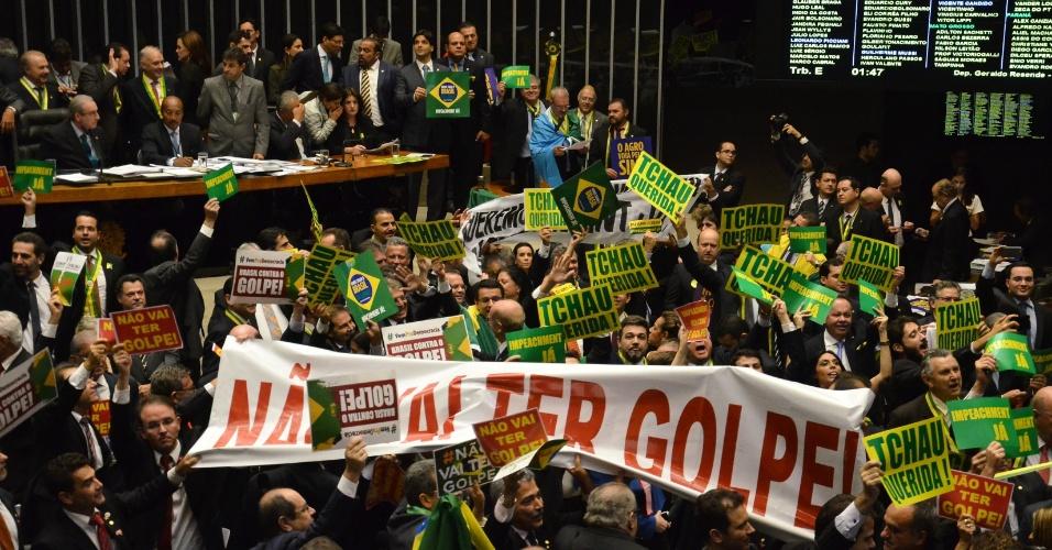 16.abr.2016 - Deputados contra e a favor do processo de impeachment da presidente Dilma Rousseff erguem faixas no plenário da Câmara dos Deputados