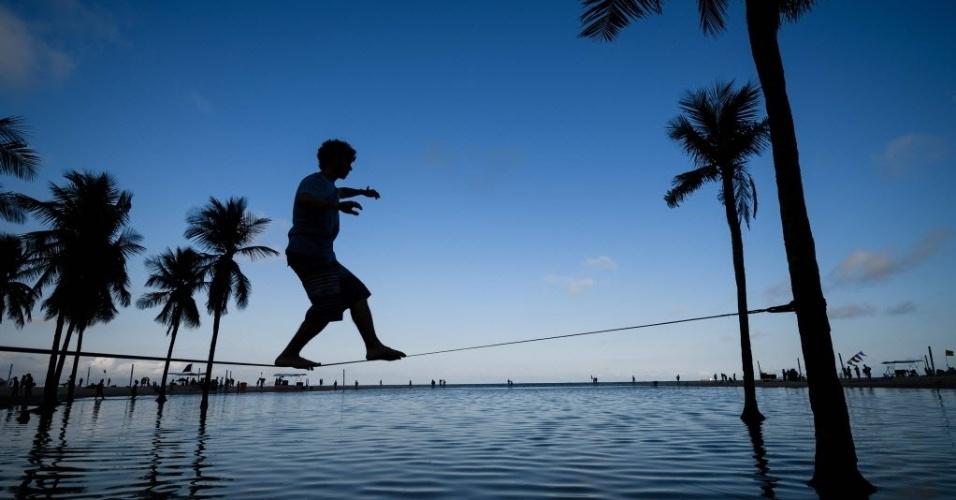 31.jul.2016 - Homen caminha em slackline entre duas palmeiras na praia de Copacabana, no Rio de Janeiro (RJ)