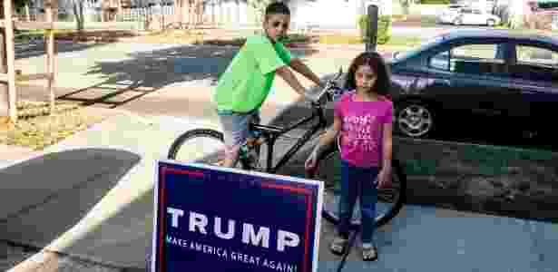 4.out.2016 - Abubeckr Elcharfa, 13, e sua irmã Maaria, 7, observam cartaz de campanha do candidato republicano Donald Trump próximo à casa deles em Staten Island,em Nova York (EUA) - Christian Hansen/The New York Times - Christian Hansen/The New York Times