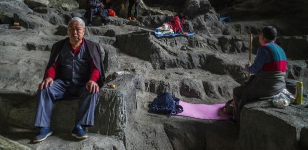 Pessoas descansando em área terapêutica, dentro da caverna Baimo, no condado de Bama, na China