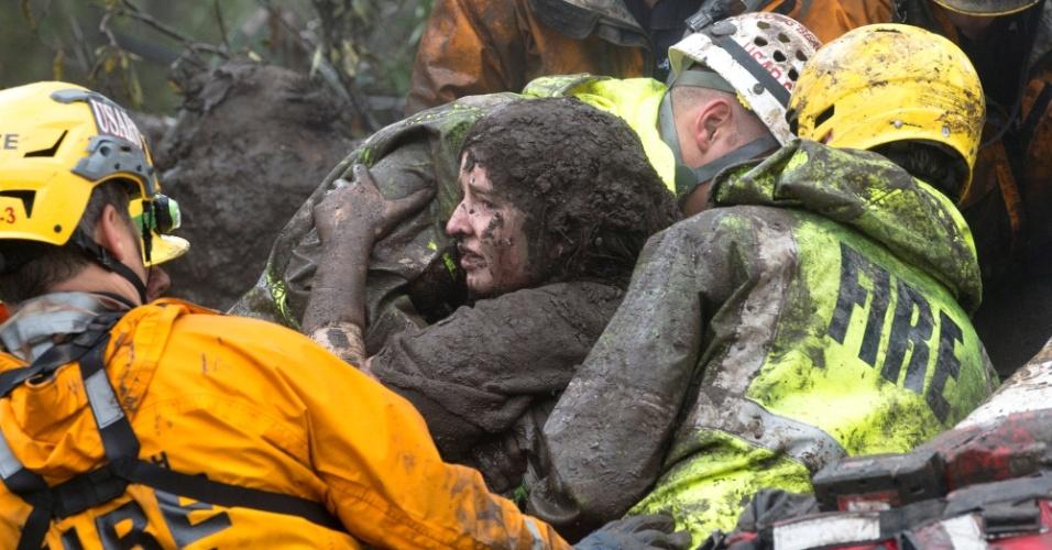 9.jan.2018 - Mulher é resgatada pelos bombeiros após um deslizamento atingir sua casa na Califórnia