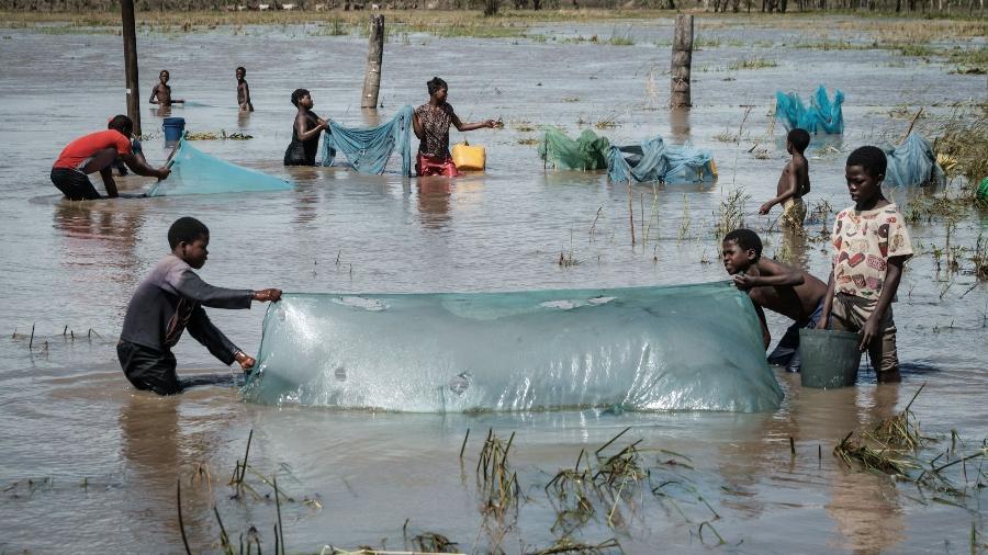 24.mar.2019 - Pessoas usam redes para pescar em uma área inundada pelo Ciclone Idai próximo a Tica, Moçambique - Yasuyoshi Chiba/AFP