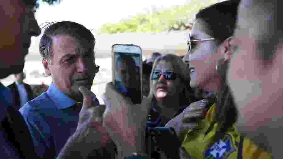 O presidente Jair Bolsonaro (PSL) cumprimenta apoiadores na saída do Palácio da Alvorada, em Brasília - José Cruz/Agência Brasil