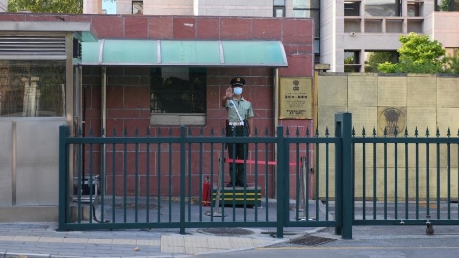Um policial paramilitar chinês vigia a entrada da embaixada da Índia em Pequim - GREG BAKER / AFP