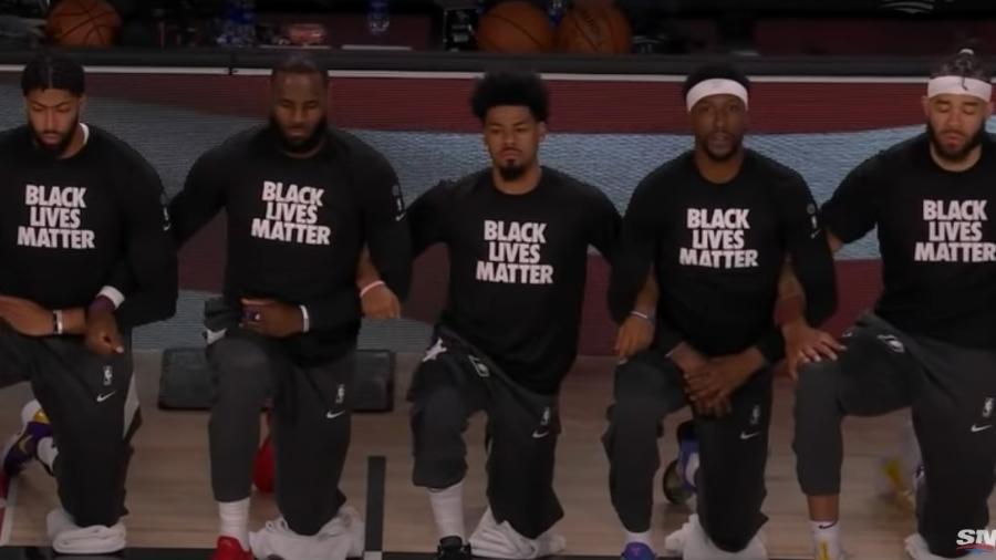 Jogadores do Lakers e do Raptors, de braços dados, se ajoelham durante hinos dos EUA e do Canadá antes de jogo entre as duas equipes - Reprodução/Youtube