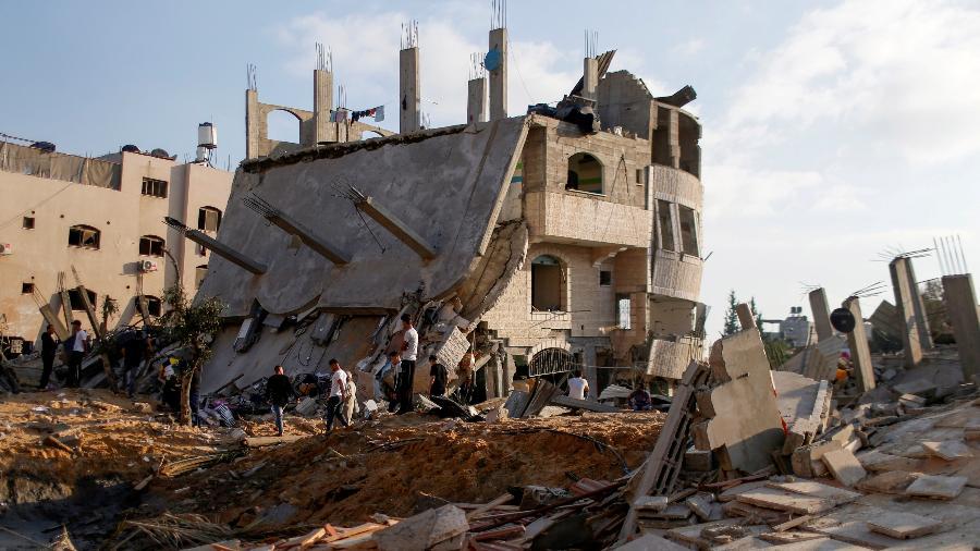 Palestinos se reúnem ao redor das ruínas de prédios que foram destruídos em ataques aéreos israelenses em meio a uma explosão de violência israelense-palestina, no norte da Faixa de Gaza - Mohammed Salem/Reuters