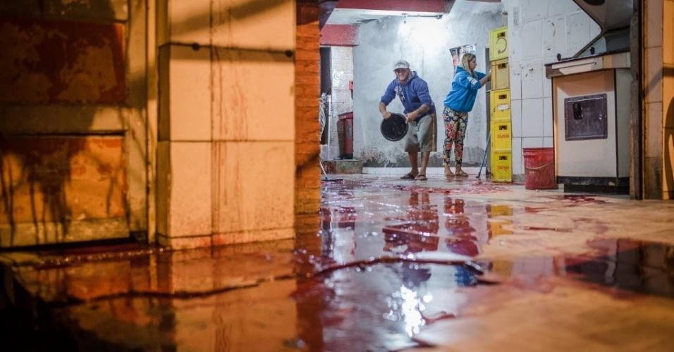 14.ago.2015 - Funcionários limpam bar após dez pessoas serem mortas no local, em Osasco, na Grande São Paulo. Ao menos 20 pessoas foram mortas e sete ficaram feridas em uma série de ataques na região, no intervalo de 2h30. Segundo testemunhas, os ataques a tiros forma realizados por homens em um carro