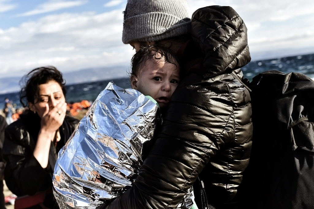 30.set.2015 - Bebê chora ao ser segurado por homem na ilha grega de Lesbos. Refugiados atravessaram o mar Egeu de bote da Turquia até a Grécia