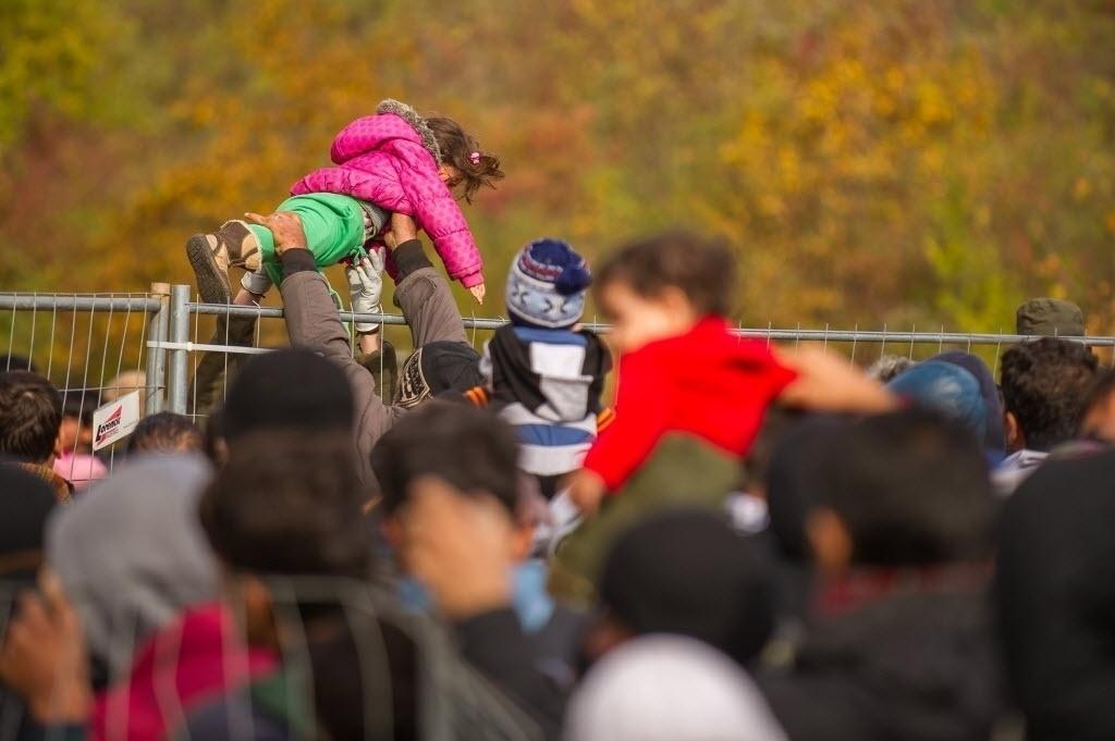 25.out.2015 - Soldado austríaco passa uma criança sobre cerca, diante de migrantes e refugiados que cruzam a pé a fronteira da Eslovênia para a Áustria neste domingo (25). A Eslovênia pediu à União Europeia forças policiais para ajudar a regular o fluxo de imigrantes