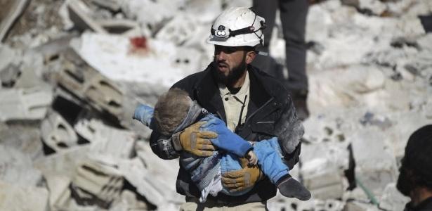 Homem carrega corpo de criança em local atingido por bombardeios, que ativistas dizem terem sido feitos por forças russas