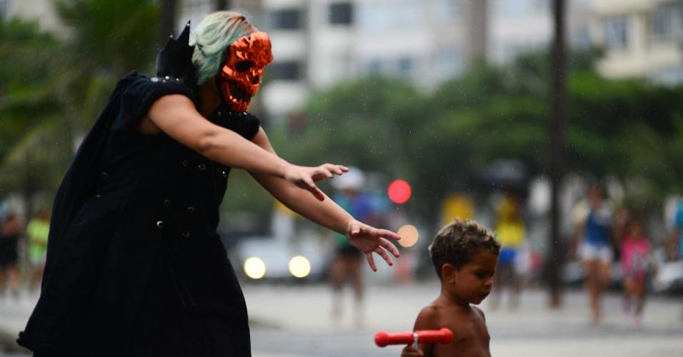 """17.jan.2016 - Homem fantasiado de demônio brinca com criança durante """"Marcha para Satanás"""", no Rio de Janeiro"""
