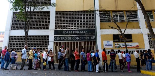 Pessoas esperam em fila do lado de fora de padaria em Caracas
