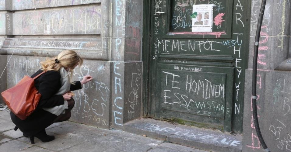 27.mar.2016 - Uma mulher escreve mensagem com giz na parede da bolsa de valores de Bruxelas, na Bélgica. O local se tornou um memorial às vítimas mortas no atentado terrorista que explodiu bombas no metrô e no aeroporto internacional da cidade