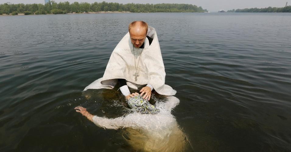 28.jul.2016 - Padre ortodoxo batiza uma mulher no rio Yenisei durante uma cerimônia que marca a cristianização do país, feita pelo príncipe Vladimir I (Vladimir, o Grande) em 988 D.C, em Krasnoyarsk, na Sibéria (Rússia)