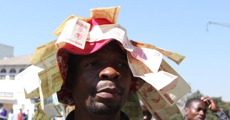 4.ago.2016 - Um homem mostra as notas do antigo dólar zimbabuense durante um protesto contra a introdução de novas notas em Harare, Zimbábue