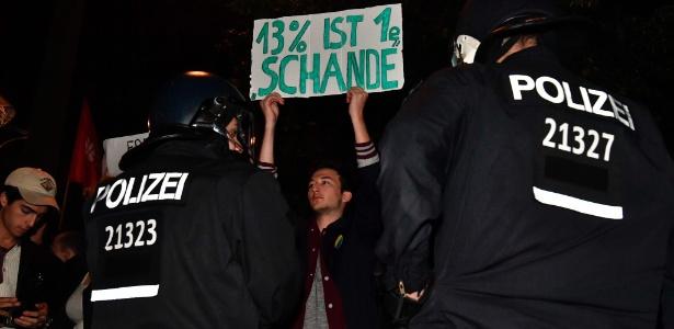 24.set.2017 - Na placa, manifestante diz que: '13% é uma vergonha'. O protesto se refere a estimativa de votos do partido de extrema direita AfD (Alternativa para a Alemanha), segundo a boca de urna
