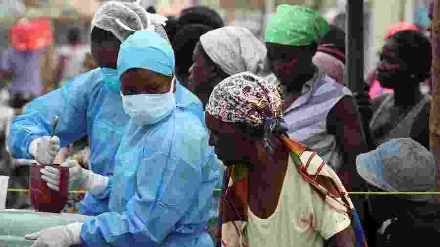 27.mar.2019 - Equipe médica mistura uma solução de cloro para distribuição num centro de saúde que lida com doenças transmitidas pela água na Beira, Moçambique - Mike Hutchings/Reuters