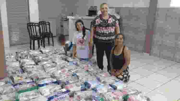 """""""No final da tarde elas me pedem, 'tia, tem um pãozinho aí para mim?' Se chega pão de doação, acaba tudo em um minuto"""", conta Maria Aparecida de Souza (de pé), líder comunitária no bairro - Arquivo Pessoal/BBC"""