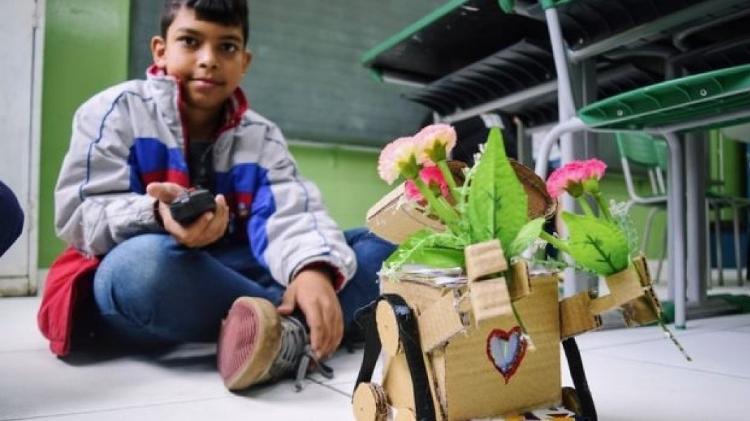Guilherme e seu Wall-e, personagem que tenta salvar as flores em um mundo cheio de lixo; na versão de papelão, ele carrega flores emprestadas pela diretora - Divulgação/Secretaria Municipal de Educação