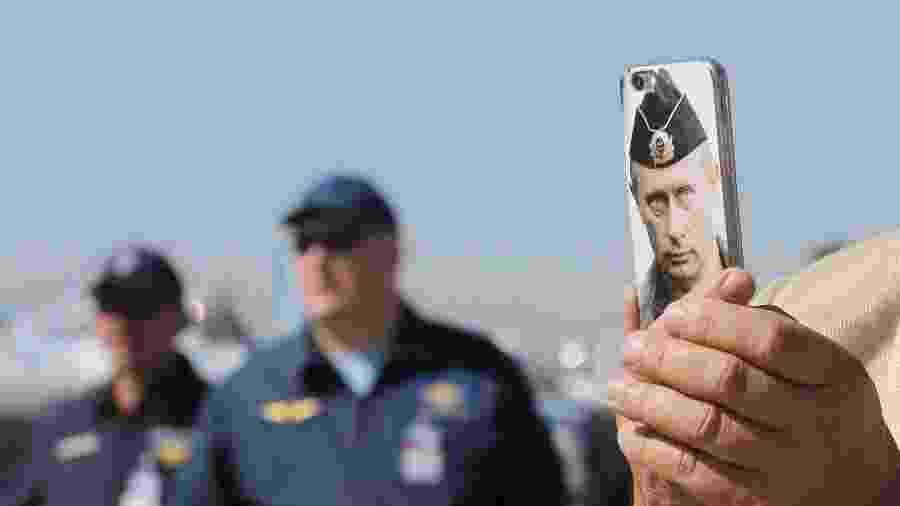 25.ago.2015 - Visitante exibe celular com imagem do presidente russo, Vladimir Putin, estampada na capa, durante o Salão Internacional de Aviação e Espaço em Zhukovsky, nos arredores de Moscou - Maxim Shemetov/Reuters