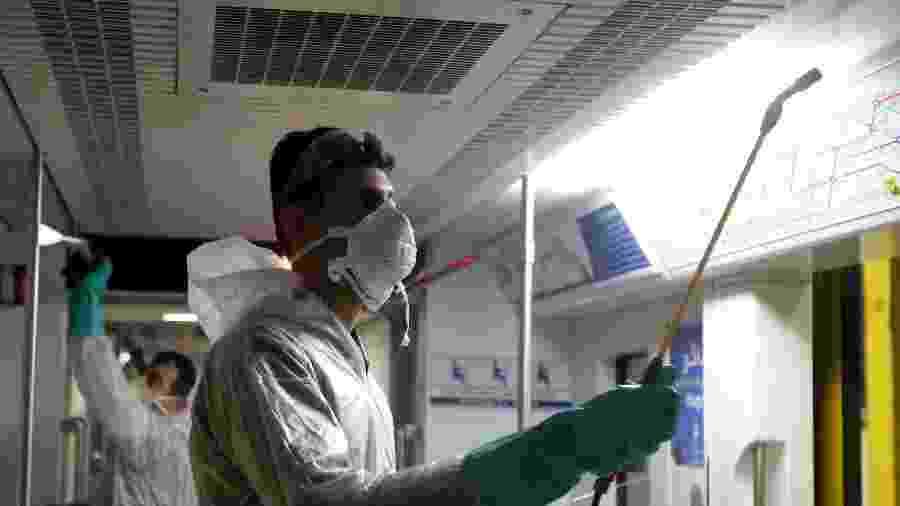 Um trabalhador do município de Teerã limpa um trem do metrô para evitar a propagação da doença covid-19 - Atta Kenare/AFP