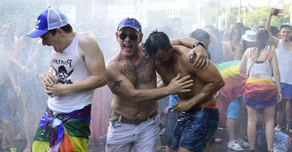 4.jul.2015 - Espanhóis se refrescam com jatos d'água lançados por bombeiros, durante a Parada Gay de Madri, na capital espanhola