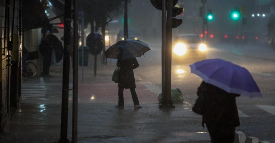8.set.2015 - Pedestres enfrentam chuva e vento forte na avenida São João, no centro de São Paulo, na tarde desta terça-feira