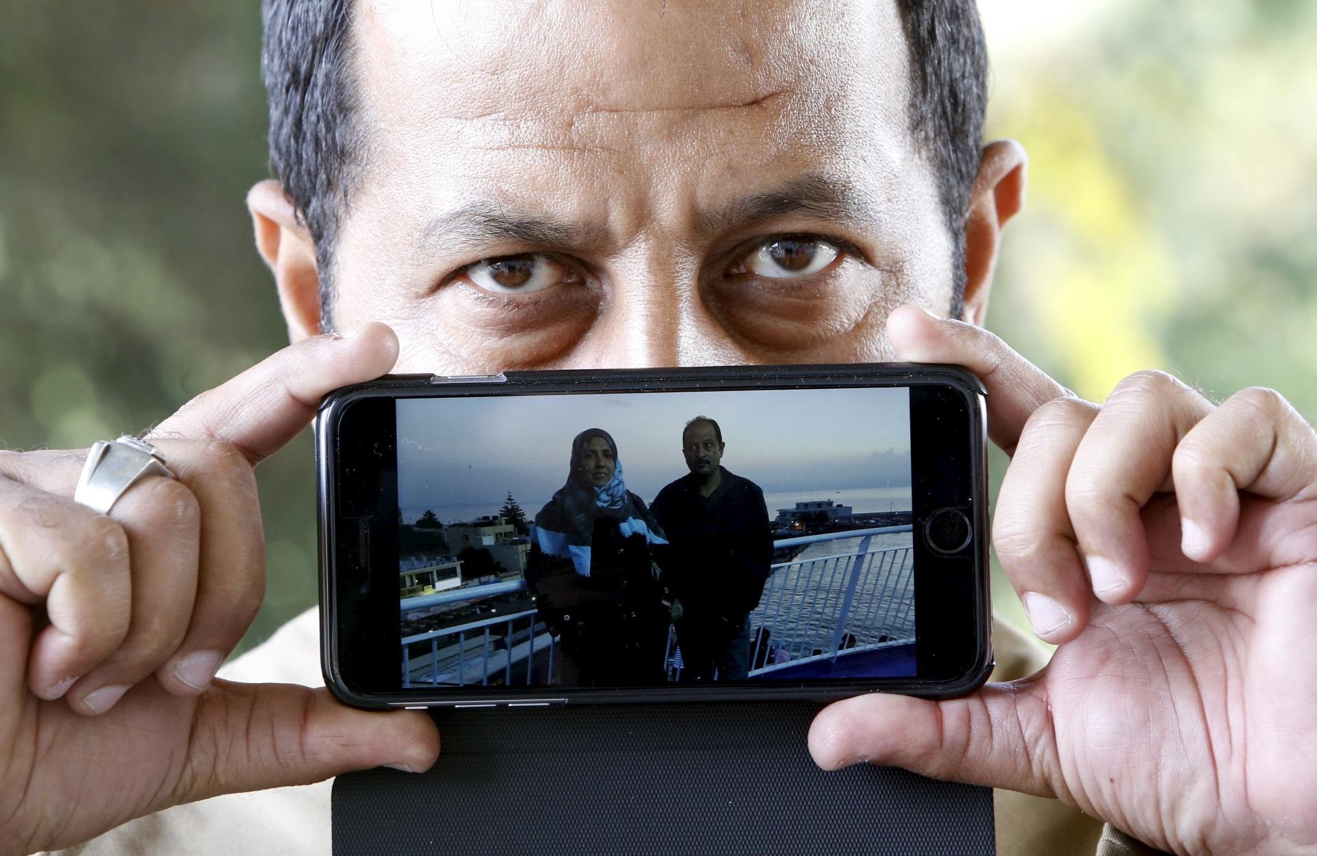 Abdullah, de Bagdá, no Iraque, mostra uma dele com sua mulher enquanto aguarda para cruzar a fronteira da Eslovênia com a Áustria