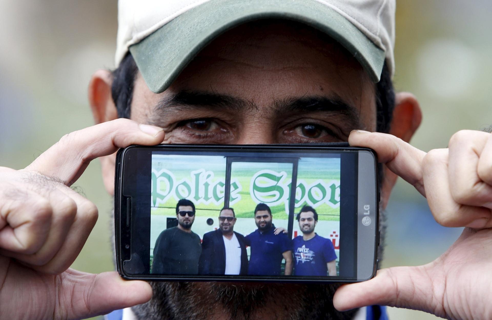Jabbar, de Bagdá, no Iraque, mostra uma imagem de seus sobrinhos enquanto aguarda para cruzar a fronteira da Eslovênia com a Áustria