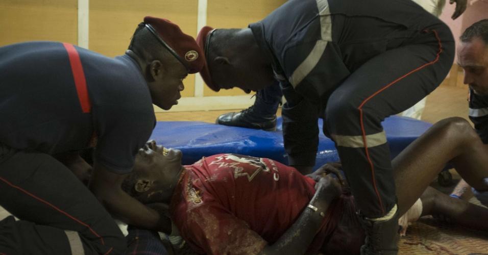 16.jan.2016 - Homem ferido é atendido por equipe médica após ataque a um hotel e café na noite desta sexta-feira em Uagadugu, capital de Burkina Fasso. O ataque, reivindicado pelo grupo terrorista Al Qaeda no Magrebe Islâmico, deixou pelo menos 20 mortos