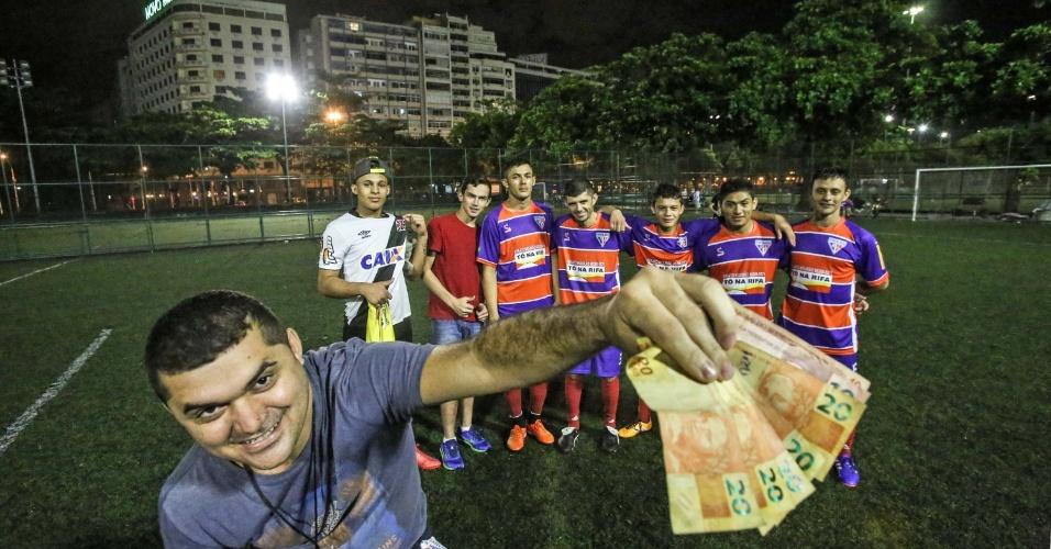 22.jan.2016 - Vencedores da partida, funcionários de uma pizzaria do Rio de Janeiro recebem o valor apostado com adversários