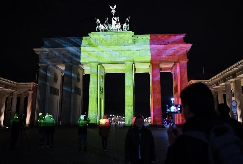 22.mar.2016 - Alemães tiram fotos em frente ao Portão de Brandemburgo, em Berlim, que foi iluminado com as cores da bandeira da Bélgica após atentado terrorista matar mais de 30 pessoas em Bruxelas