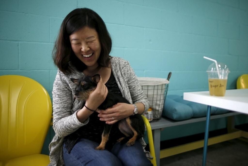 8.abr.2016 - Mulher abraça um cachorro durante a inauguração do Dog Café, um café onde as pessoas podem conhecer e adotar cães de abrigos de Los Angeles, na Califórnia, Estados Unidos