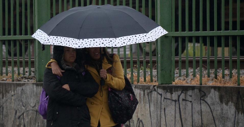24.mai.2016 - Pedestres se protegem da garoa e do frio na região da Lapa, próximo ao Mercado da Lapa, em São Paulo. A cidade registrou nesta terça-feira (24) a madrugada mais fria do ano, em média, 9,3°C, de acordo com informações do CGE (Centro de Gerenciamento de Emergências), da prefeitura. A temperatura oscilou entre 7,5°C e 10,9°C. Frio que, um pouco mais suave, vai continuar até o feriado, que deve ter também períodos de chuva