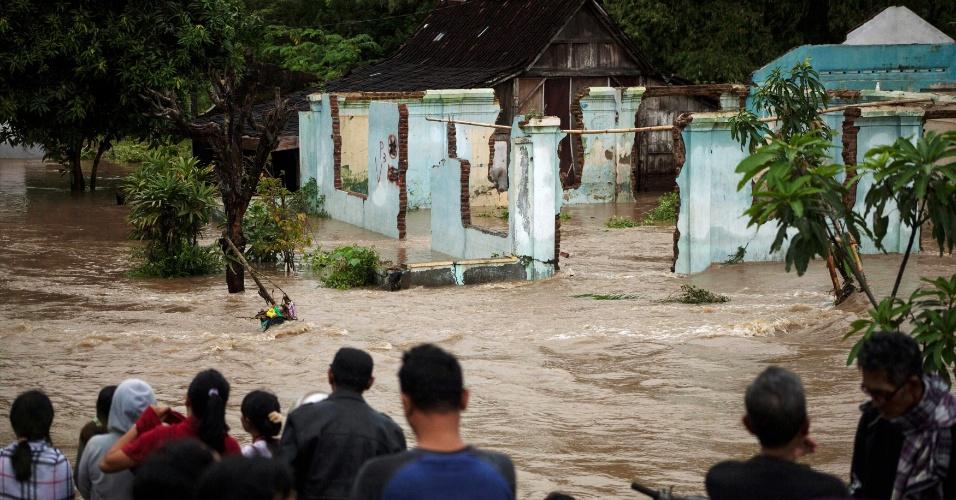 19.jun.2016 - Moradores aguardam à beira de rua inundada na cidade de Kampung, na Indonésia. A região vem sofrendo com as fortes chuvas que atingem o país asiático