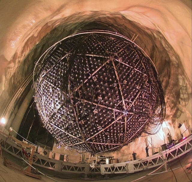 20.jun.2016 - Uma parte das partículas fantasmas é produzida em reações nucleares dentro do Sol, outra parte é criada na atmosfera terrestre com a incidência da radiação cósmica. Mas os únicos lugares onde elas são visíveis são nos detectores instalados em lugares naturalmente protegidos de qualquer tipo de interferência. O Snolab (Canadian Sudbury Neutrino) fica enterrado há cerca de 2 km em solo canadense. O detector foi responsável por descobrir que existem ao menos três tipos diferentes de neutrinos, que vão para frente e para trás enquanto aceleram pelo espaço. O laboratório estuda as partículas fantasma com uma esfera plástica preenchida com mais de 700 toneladas de um fluído especial que detecta partículas. A esfera é revestida de água e pendurada por cordas. Quando os neutrinos interagem no detector, eles produzem uma luz, que é analisada por cerca de 10 mil sensíveis detectores de luz instalados no local