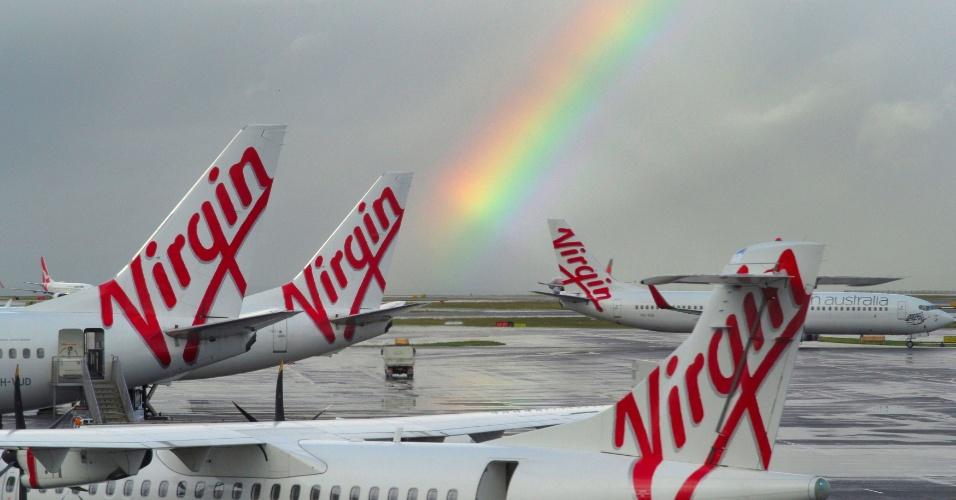 5.ago.2016 - Arco-íris se forma no aeroporto de Sydney, na Austrália. A Virgin Galactic, pertencente à Virgin, do bilionário britânico Richard Branson, anunciou que recebeu, da FAA (o órgão que regula a aviação nos EUA), uma licença de operação para seu foguete SpaceShipTwo, voltado para o turismo espacial