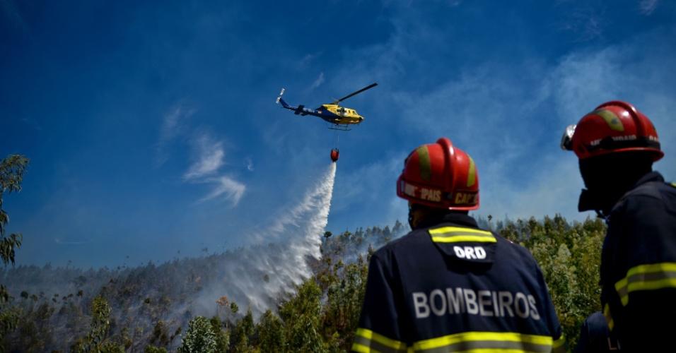 9.set.2016 - Bombeiros trabalham próximos ao helicóptero que joga água para acabar com incêndio em Monchique, em Portugal. A região turística foi atingida por incêndios florestais violentos que levaram a evacuação de um hotel de luxo e três aldeias