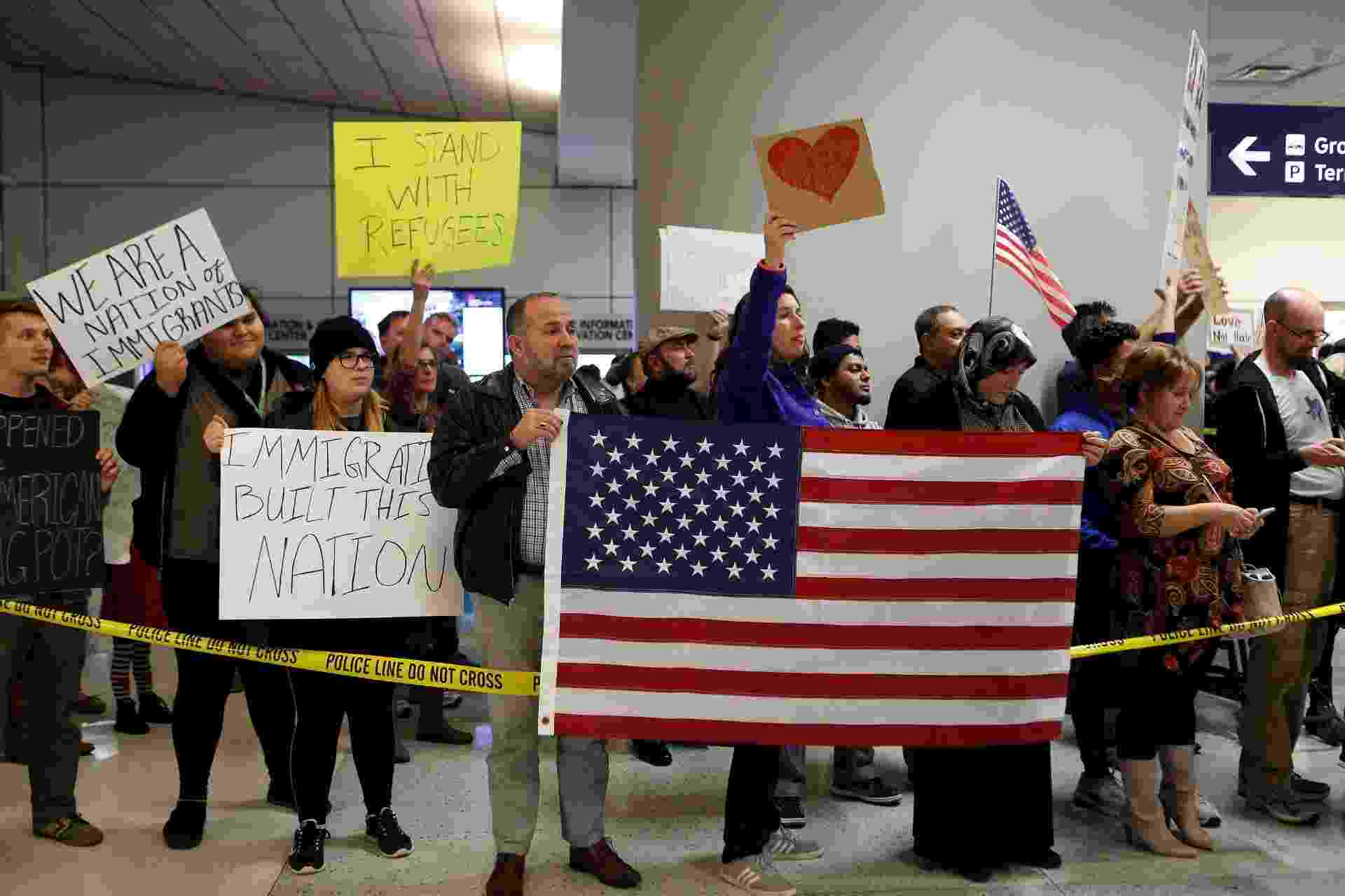 29.jan.2016 - Manifestantes protestam contra bloqueio a imigrantes determinado por decreto do presidente Donald Trump no aeroporto internacional de Dallas, no Texas. A nova regra impõe controle por três meses contra viajantes procedentes de Irã, Iraque, Líbia, Somália, Síria e Iêmen - Morty Ortega/AFP