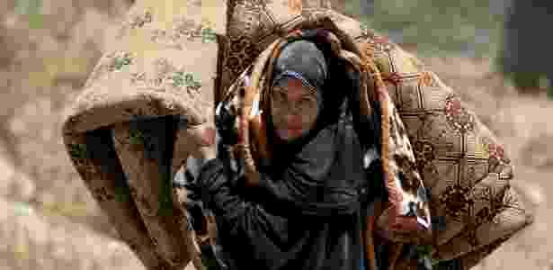 Mulher carrega colchão ao deixar sua casa em distrito da cidade antiga de Mossul - Alaa Al-Marjani/Reuters