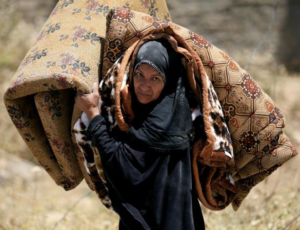 Mulher carrega colchão ao deixar sua casa em distrito da cidade antiga de Mossul