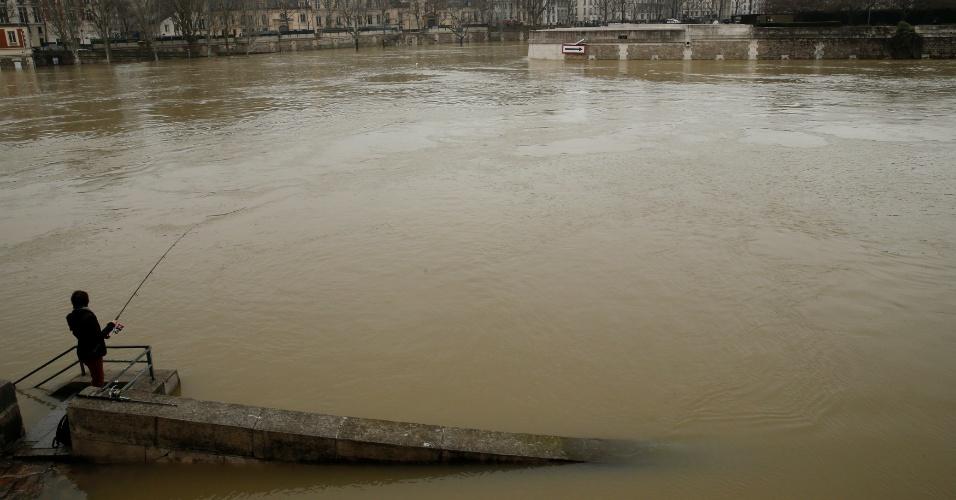 27.jan.2018 - Homem aproveita a cheia do rio Sena para uma pescaria neste sábado. Paris enfrenta risco de inundação