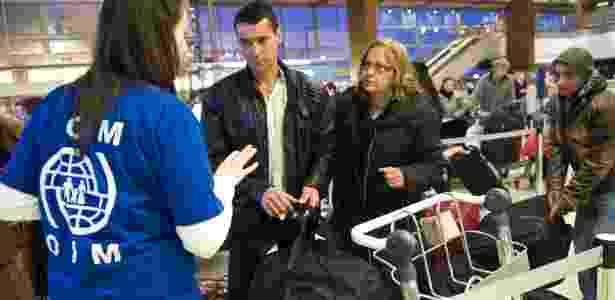 Funcionária da Organização Internacional para as Migrações (OIM) dá orientação em aeroporto português - OIM / Reprodução
