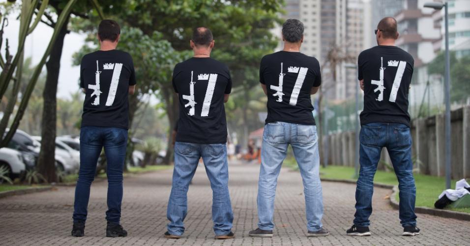 Eleitores do presidenciável Jair Bolsonaro (PSL) posam de costas mostrando o número do candidato (com uma arma no lugar do 1)