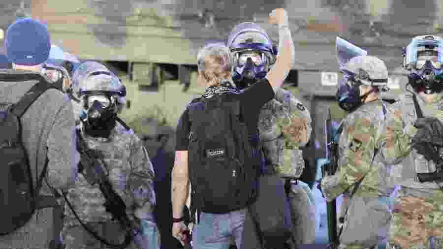 Manifestante ergue o braço em frente a agentes da Guarda Nacional em Minneapolis - Tannen Maury - 29.mai.2020/Efe