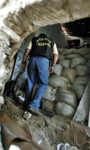 Membro da Polícia Federal observa terra retirada do túnel pelos ladrões para efetuar o roubo no Banco Central de Fortaleza (CE) em 2005. O sistema de segurança interno usado para proteger o cofre-forte do Banco Central de Fortaleza, que guardava R$ 164 milhões, não gravava as imagens de dentro do local, apenas as exibia a um vigia, e não foi acionado o alarme